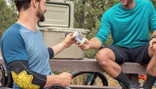 Deux hommes partagant une bière sortie d'une glagcière électrique